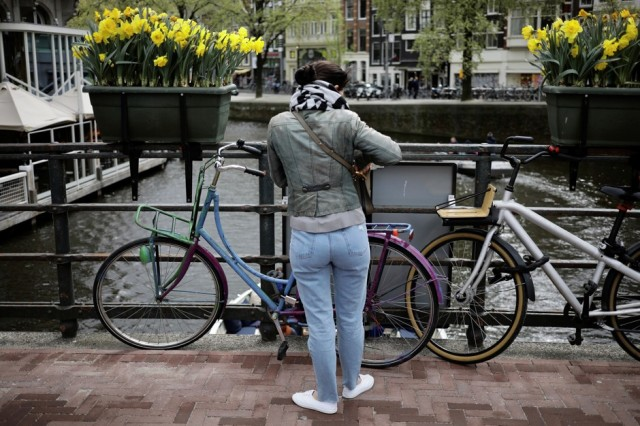A woman parks her bike beneath boxes of daffodils on a bridge in Amsterdam