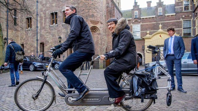 Photo of Dutch politician Jetta Klijnsma and a disability advocate on a tandem bike with a wheeled walking frame on the back.