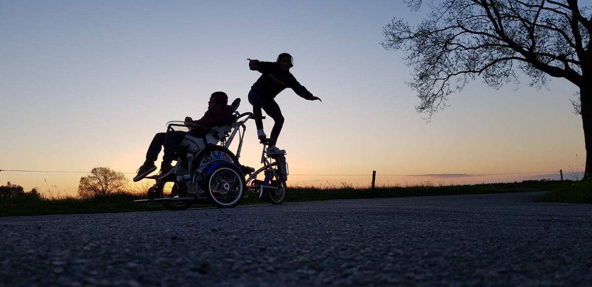 Photo of a young man cycling around with his brother in a mobility chair.